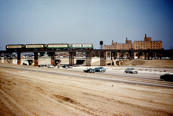 "#22 - A train of westbound 4000s has ascended the ramp from the last grade crossing at California and is crossing the unlandscaped expressway to join the old Garfield Park ""L"" structure near Sacramento Blvd. Answer: May 25, 1956 (Photo by Charles Able)"