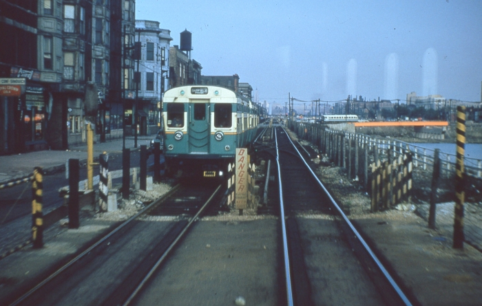 #19 - Early flat door 6000 train westbound on Van Buren at the Campbell scissors crossover. A bus is going north on Western, with the steel of the new bridge in evidence. Answer: May 9, 1954 (Photo by Ray DeGroote)