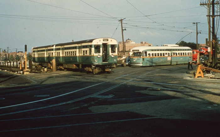 "#1 - Green Hornet ""L"" car meets Green Hornet streetcar. The earliest of the rapid transit 6000s with flat doors and double headlights is seen eastbound on Van Buren Street at Western Avenue as Garfield Park. Postwar St. Louis PCC 4273 is northbound on the Western Avenue shoofly, constructed while the bridge over Congress is built. The ""normal"" streetcar tracks are seen in the foreground. This would be 1955 or 1956, after 6000s came to Garfield and before Western was bussed, June 1956. Answer: CTA 6000s and 4393 at Western/Van Buren on June 16, 1954. (Photo by Bill Hoffman)"