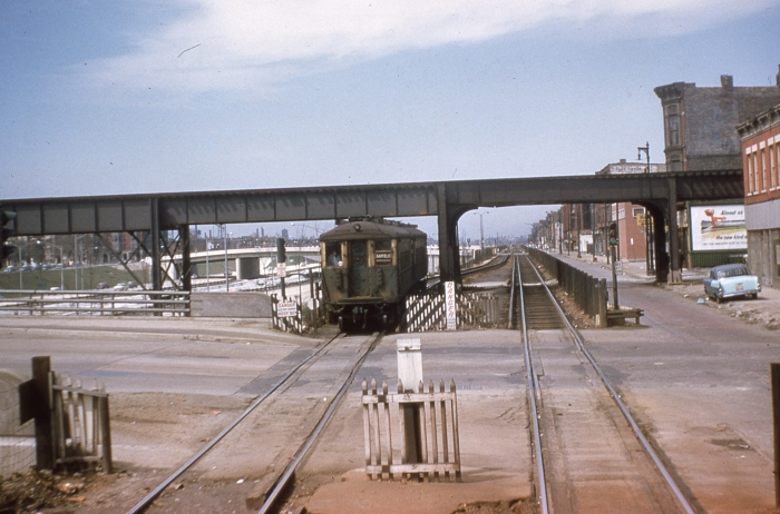 #16 - An eastbound 4000-series train is on Van Buren Street at Paulina. The 4000s represented the middle years of the street level operation, bridging wood cars (early) and 6000s (later). The new structure for Douglas trains is behind the facing train. Paulina's streetcar tracks are no longer evident. Answer: CTA 4446 at Van Buren/Paulina on April 21, 1957. (Photo by Ray DeGroote)