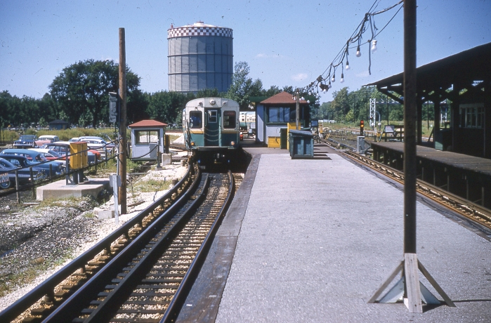 "#14 - A view of Desplaines Avenue station, now part of CTA's West-Northwest route. A 6000 series train is facing the camera, signed Congress ""A"", with the famous Maywood gas tank in the background. The station has been reconfigured for CTA-only operation. The platform at the right is from the 1953-1957 era, minus the CA&E ticket office and waiting room. The Congress ""A"" sign places this in the post June 1958 era. Answer: September 6, 1961. (Photographer unknown)"