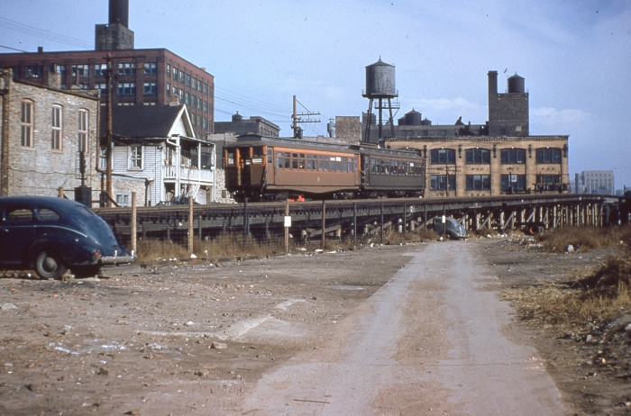 "#12 - Two similar Met woods, one early with the fishbelly underframe, the later version with the straight frame, descend the east ramp from the Met ""L"" mainline, approaching the first grade crossing at Racine Avenue, probably early on in this operation, since Garfield Park was operated exclusively with wood cars. Answer: CTA 2815-2880 westbound, descending ramp to Van Buren near Racine on November 8, 1953. (Photo by Ray DeGroote)"