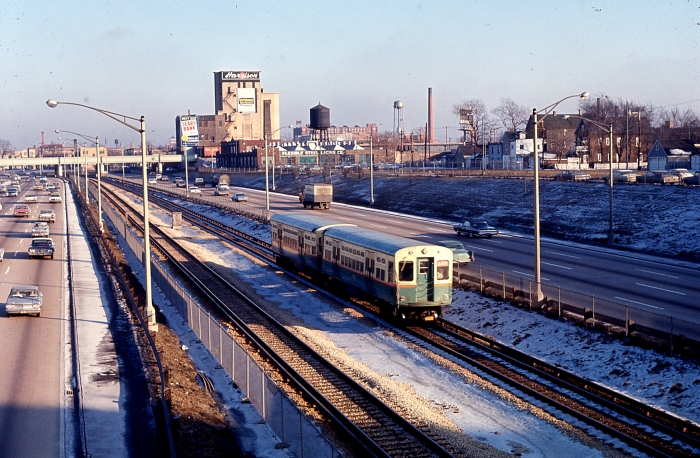 "#7 - The Garfield Park ""L"" is but a memory. Here we see an eastbound Congress ""A"" train, consisting a later 6000s cars with curved doors, probably taken from the Cicero Avenue overpass with the Belt Railway overpass in the background. This must be late 50s or early 60s, with the vulgar styling of Detroit-made cars in evidence. Answer: Congress expressway at Cicero on December 27, 1963. (Photographer unknown)"