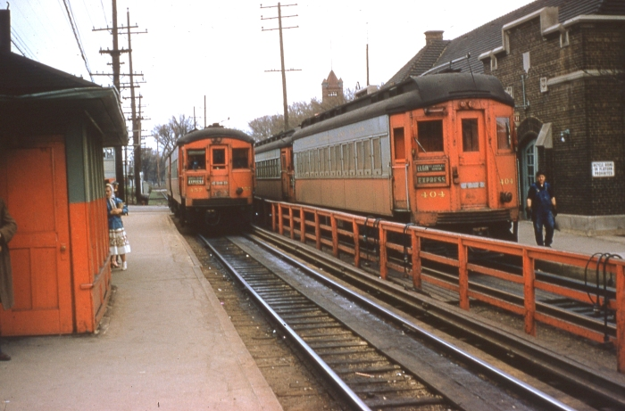 #3 - An almost timeless photo of CA&E 457 and 404 at Wheaton station, the hub of CA&E operations. The woman's babushka suggests late spring or early fall. The key clue to time would be knowing when 404 received the final paint job and, of course, no later than July 3, 1957. Answer: CA&E 457 at Wheaton on April 21, 1957. (Photo by Ray DeGroote)