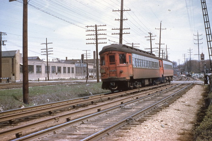 #2 - Two car Chicago Aurora & Elgin train headed by Cincinnati steel 422 with a postwar St. Louis steel westbound on CA&E tracks in Wheaton. The approximate location, as determined through Googole Maps, is about 188 S. Wheaton Ave., the current location of the Illinois Prairie Path. (Mr. Foelschow thought this was Forest Park, but the buildings in the picture match up with Wheaton. The other tracks at left are the C&NW (present-day Union Pacific West Line). Answer: CA&E 457-422 at Wheaton on April 21, 1957. (Photo by Ray DeGroote)