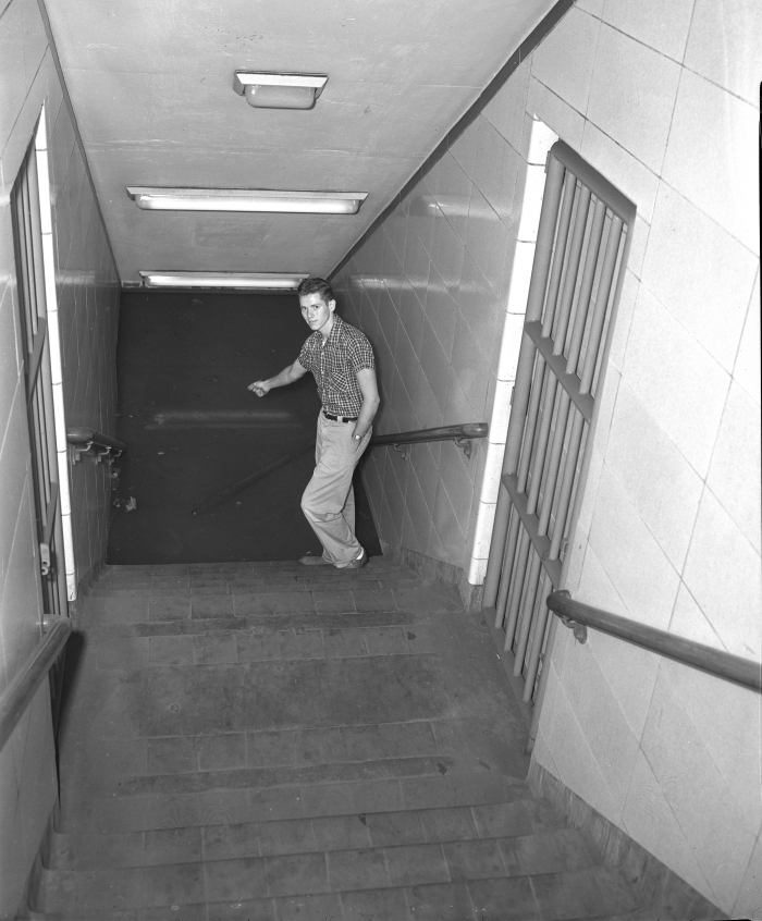Dennis Headley, CTA ticket agent, points to the flooded subway at the LaSalle and Congress station on July 13, 1957. (Editor's collection)