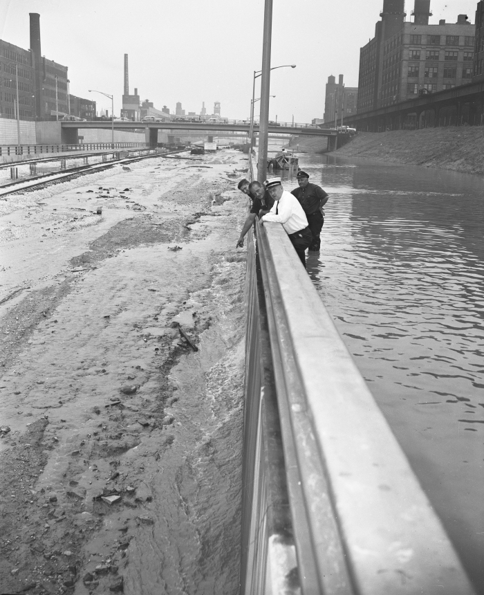 "Ist Division Fire Marshall Frank Tokars and a crew of firemen survey the pumping project on the Congress expressway at Halsted. Water was overflowing from the expressway in the CTA section where the ""L"" trains would tie in with the subway the following year. (Editor's collection)"