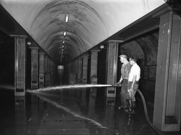 Workmen William Metzger and Dennis Moriarty wash down the muck left by the flood on the platform of the subway at Congress and LaSalle streets on July 14, 1957. (Editor's collection)