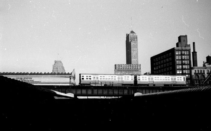 """Frame 9 - """"6000-series train, presumably Douglas, on Met """"L"""" mainline east of Canal. over Union Station trainshed, viewed from Van Buren Street in front of the Main Post Office."""" -GF"""