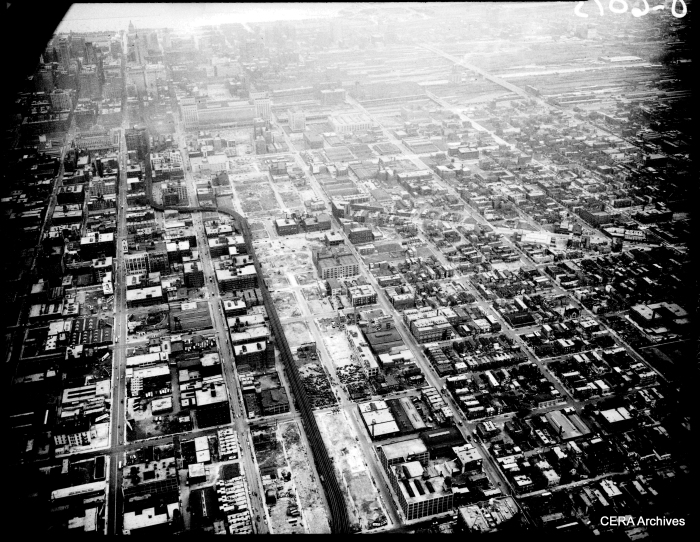 "An aerial view (looking east) of the Garfield Park ""L"" and the future site of the Congress Super-Highway on September 2, 1950. If you look closely, you can see that some demolition has already taken place. The highway follows the path of the ""L"" in the foreground, heading straight through the middle of the old Main Post Office in the background."