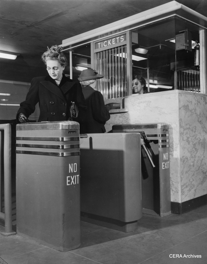 "October 21, 1943 - ""The stile at left operates with a dime, while the ticket seller turns the one at the right from her booth for passengers using transfers or those requiring change."""