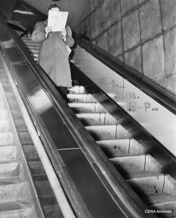 "A Chicago subway scene on December 23, 1943. ""Escalator all to himself, post-midnight customer reads while he rides. No din, no shove."""