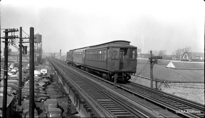 In the early 1950s, a westbound Garfield Park train descends the ramp between the Cicero and Laramie stations.