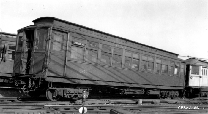 "CRT Metropolitan Division 2877, shown here in a photo by La Mar M. Kelley, was built in 1906. CERA Bulletin 113 describes this order as ""the enclosed vestibule type with manually controlled pneumatically-operated sliding doors and with steel and wood underframes and steel-reinforced wooden bodies."" Work car 2721 is at the rear."