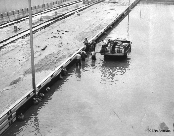 CTA workers sandbag retaining wall of westbound expressway on west side of Halsted (July 13, 1957).