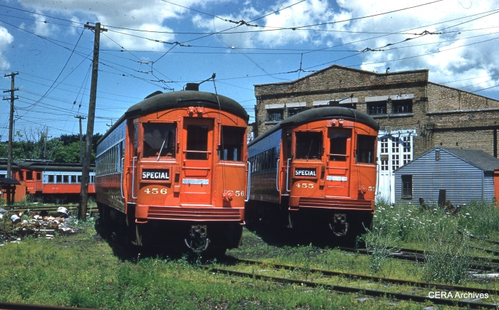 "CA&E 456 and 455 among the weeds at Wheaton Shops in August 1959. Even freight service had ended a few months earlier, but these cars look like they have received a fresh coat of paint, in hopes of being sold to another operator. Although the cars were only about 12 years old at this time, six of the ten postwar units ended up being scrapped a few years later right on this spot. The only cars saved from the 451-460 series went to ""Trolleyville USA"" in Ohio instead of ending up on the North Shore Line or in Airport service in Cleveland."