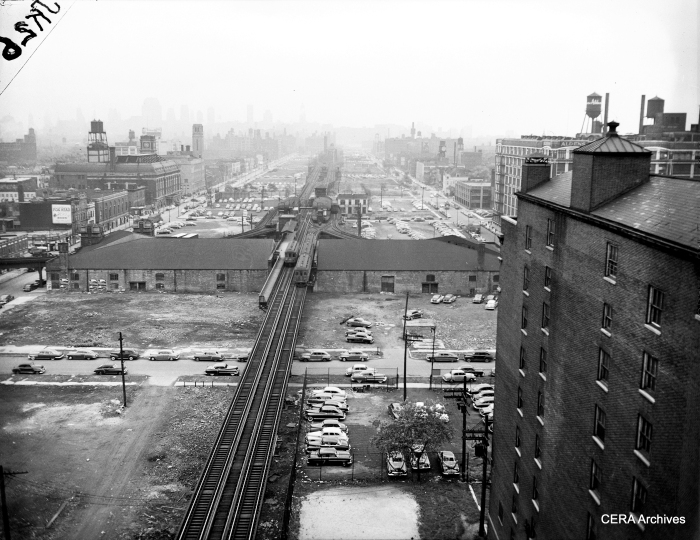 "In this circa 1952 aerial photo, we are looking east near Marshfield Junction, where the three Met ""L"" branches split off from each other. By this time, the Dearborn subway had opened, leaving the branch at left only for shop moves. Two CA&E trains pass each other, while two CTA trains are in the station. The building in the foreground will need to be torn down soon to make way for the expressway. (Photographer unknown)"