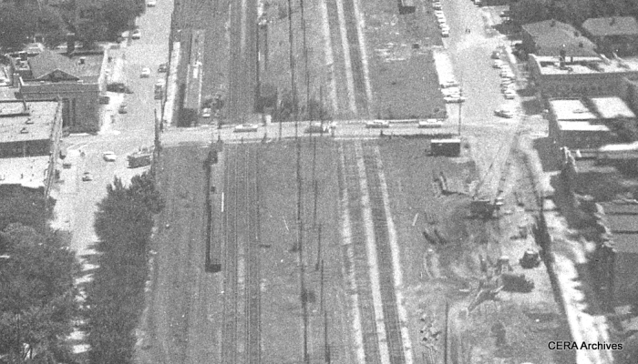 A close-up view showing the CTA's temporary station at Oak Park avenue on July 25, 1957. The B&O freight tracks are at right. Everything here is still at ground level.The CTA tracks have been moved to the north. Note that the eastbound and westbound platforms are on opposite sides of Oak Park avenue. The highway would not open in this area until more than three years later. (Photo by Burley)