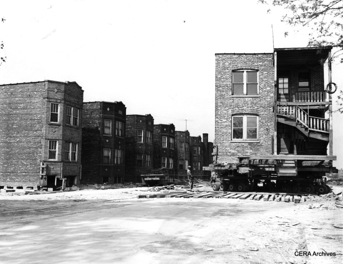 "May 21, 1954: ""Here's a picture of a neighborhood 'on the move.' This two-flat is one of seven similar buildings in the 4900 block on Lexington moved from north to south side of street to make room for Congress st. expressway. Building was turned in middle of the street to slide it on new foundations at 4927 Lexington. Structures are moved on rubber-tired dollies lashed to the underside of steel and timber supports."" (Photo by Frank Las)"