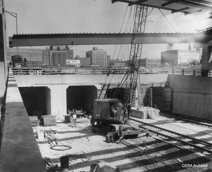 """June 10, 1958 - 'Pictorially, you are """"entering"""" Chicago's new CTA subway which will open June 22. The subway proper runs under the Congress Expressway from Halsted to link with the Dearborn-Milwaukee subway at Dearborn. Trains will enter the subway from an open cut in the expressway, on which they will travel from Lockwood (5300 west). Ultimately the western terminal of the expressway run will be at Desplaines av., Forest Park. From Lockwood to Dearborn, the trains will take just 14 minutes. The scene here is looking east from Halsted at the start of the subway proper. A crane hoists a beam into place for auto traffic interchange at this point."""" (Photographer unknown)"""