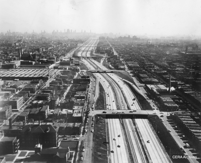 """In this January 1958 view, we see both the unfinished Congress median line and the Garfield Park """"L"""". Just above the middle of the photo, the """"L"""" crosses from the north to the south of the expressway at Sacramento. Motorists apparently had to dodge support columns right in the middle of the highway. The """"L"""" section at right continues west before crossing the highway yet again, while at left trains descend a ramp down to temporary trackage in Van Buren street. (Photographer unknown)"""