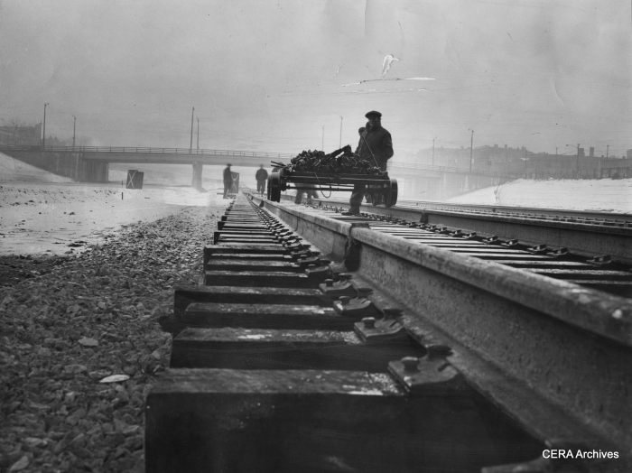"""February 9, 1956 - """"Congress at expressway about 2900 west. Workmen brave the bad weather to continue completion of rails on the Congress st expressway. They fasten down rails with brackets and spikes."""" (Photo by Larry Nocerino)"""