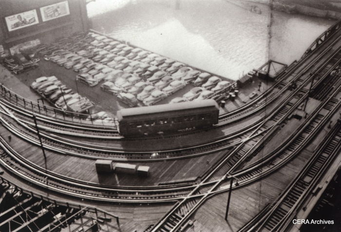 """A lone Met """"L"""" car heads toward the Loop in 1949. There were four tracks crossing the Chicago River at this point, on two parallel bridges. The tracks at the bottom of the picture led to the Wells St. terminal. In 1955, the tracks at left were torn out due to the construction of this part of Lower Wacker Drive, and a new connection to the Loop """"L"""" was created by bridging the short gap with the gutted Wells St. Terminal. (Photo by Stanley Kubrick)"""