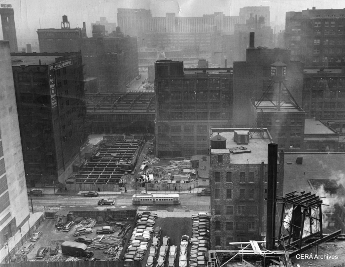 """March 11, 1949 - """"Land that once was congested with Loop skyscrapers appears now as a deep cut through the Loop looking west from a building on Dearborn st. The new superhighway, eight lanes wide, will pass under the LaSalle st. station tracks, over the river and through the arcade in the Post Office (background). The cleared site in the immediate foreground once was the location of the 13-story Monon building, since razed by the Dept. of Subways and Superhighways. (Unknown Photographer) Note the PCC streetcar."""