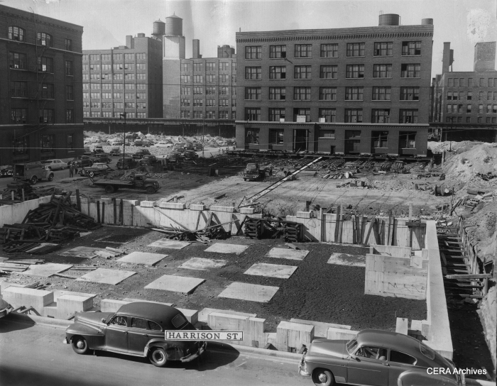 """September 2, 1949 - """"Arrow indicates path in which five-story building is being moved from Congress and Peoria sts. to its new foundation (foreground) at Harrison and Peoria sts. to make way for Congress st. superhighway."""" (Photographer unknown) The Garfield Park """"L"""" is visible in the background."""