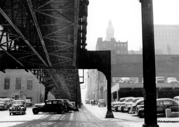 "Mystery Photo #10 - ""This is the Guilford Ave. ""el"" Saratoga St. ramp in Baltimore. Service on this line ended on 1-01-50."" (Unknown photographer) This was somewhat of a trick question. We did say, however, that the photos were ""generally"" from Chicago. While this scene does look like Chicago, none of our ""Ls"" descend right into the middle of a street as this one did. The difference, of course, is that this was a streetcar elevated. So it naturally went into a street. Baltimore's el was 2000 feet long. Kansas City had a similar mile-long el."
