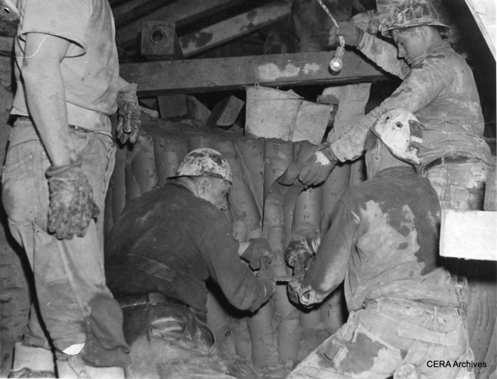 "January 10, 1939 - ""Because Chicago's subway is being dug at a depth of 35 feet, where there is clay instead of rock, it is being dug with knives. Curved blades about a foot long, with a handle at each end, are held by two men while a third one pushes the knife downward to slice off a long strip of clay. It was found that this is the fastest way to cut through clay. Three 'groundhogs' are shown above using one of the knives."" (Photographer unknown)"