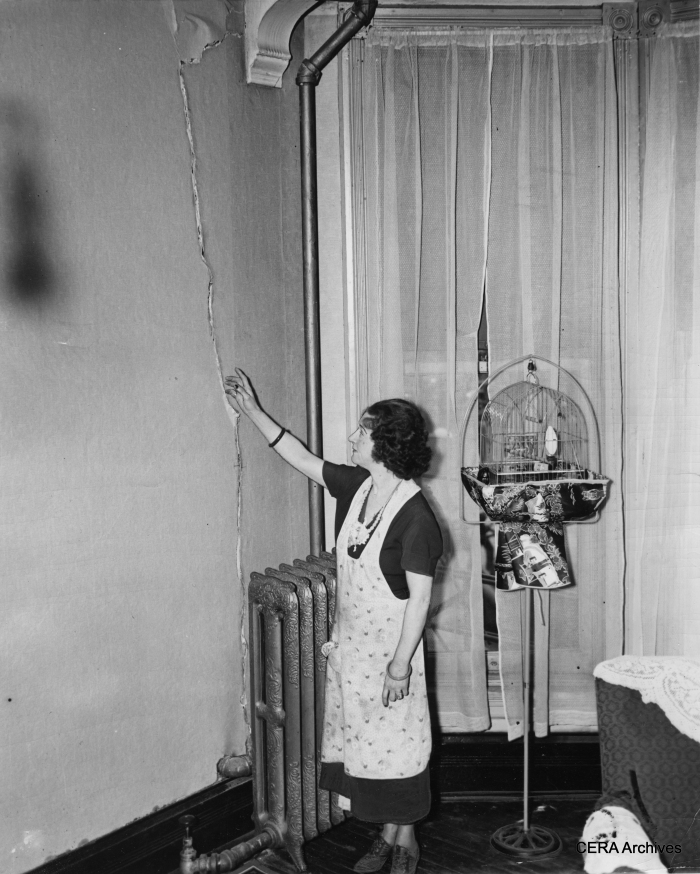 "May 17, 1939 - ""Lillian Edwards looking at crack in wall in her apartment, caused by subway construction."" (Photo by Padulo)"