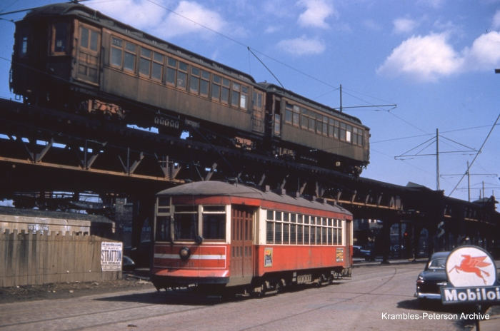 """In this classic photo by George Krambles, an """"L"""" train led by car 1753 passes surface car 3136 in April 1952."""