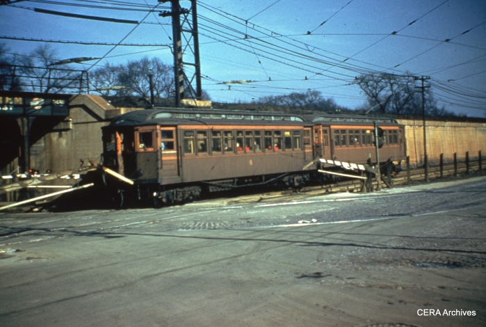 """Wooden """"L"""" cars cross the #16 streetcar line at Pine. (Unknown Photographer)"""