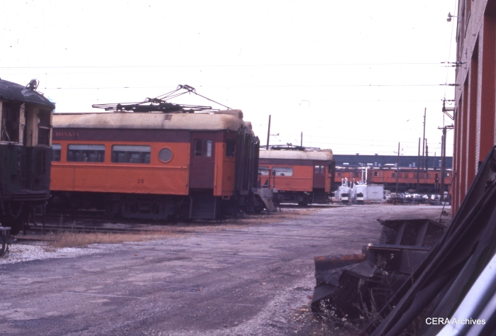 "South Shore cars 26 and 102 in Michigan City, October 1975. A CTA 4000-series ""L"" car is barely visible at left, on its way to a railway museum. (Photographer Unknown)"