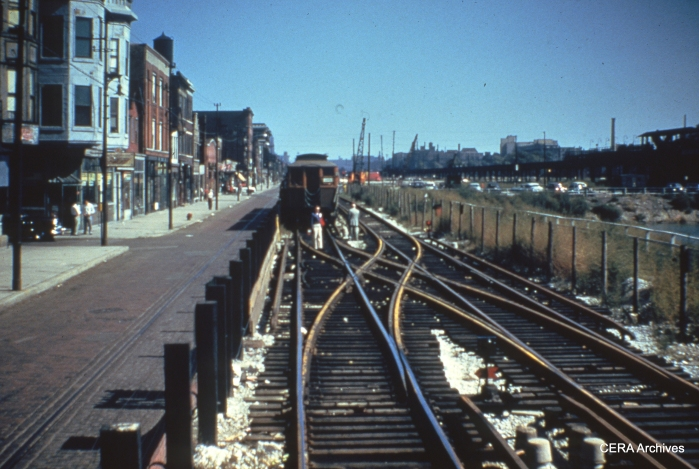 "From the sign on the wooden ""L"" car, this must be a CTA test train on the temporary Van Buren Street trackage, just prior to the beginning of service in September 1953. Streetcar tracks are still visible in Van Buren Street. (Photographer unknown)"
