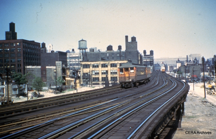 "A two-car train of CTA woods heads west on the Garfield ""L"", somewhere east of Marshfield Junction. (Photographer unknown)"