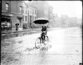 Image of a man holding an umbrella while riding a bike in the rain along an street during a street car strike in Chicago, Illinois. Street car tracks are visible on the street. View looking across the street with man at an angle to the camera. [ca. 1915 June 15] Chicago Daily News negatives collection, DN-064587. Courtesy of Chicago History Museum.