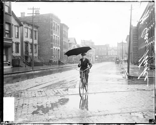 Image of a man holding an umbrella while riding a bike along an street in the rain during a street car strike in Chicago, Illinois. Street car tracks are visible on the street. View looking down the street with the man facing the camera. [ca. 1915 June 15] Chicago Daily News negatives collection, DN-064588. Courtesy of Chicago History Museum.