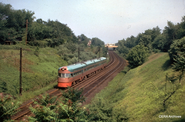 A CNS&M Electroliner speeds through the open cut in Evanston.  The former Asbury station is visible in the background. (CERA Archives)