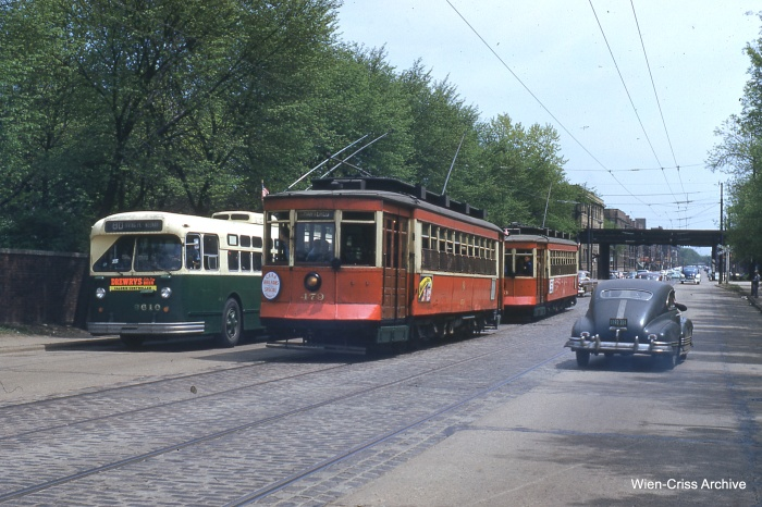 "A CTA #80 trolley bus, running on parallel wire, passes the fantrip cars on Irving Park Road just west of the North side ""L"". There were very few sections of shared wire between streetcars and trolley coaches on the CTA system. Note the grade crossing underneath the ""L"", leading to Buena Yard. (Bill Hoffman Photo - Wien-Criss Archive)"
