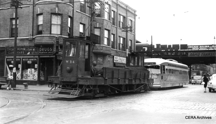 """CSL W14 towing a PCC northbound at Kedzie and Harrison in 1947. As you can see by the sign, Chicago, Aurora & Elgin trains stopped at the Kedzie """"L"""" station on the Garfield Park line. (Joe L. Diaz photo, CERA Archives)"""